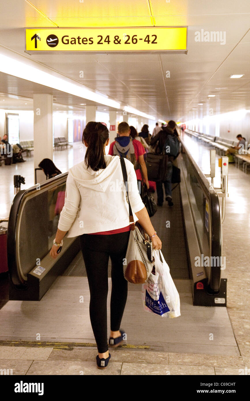 A young woman going to her gate for her flight, Terminal 3, Heathrow airport London UK - Stock Image