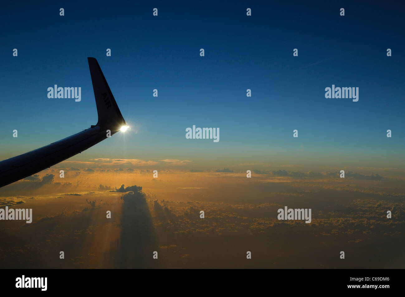 Wing tip of Boeing 737-800 airliner plane at sunset over Atlantic Ocean - Stock Image