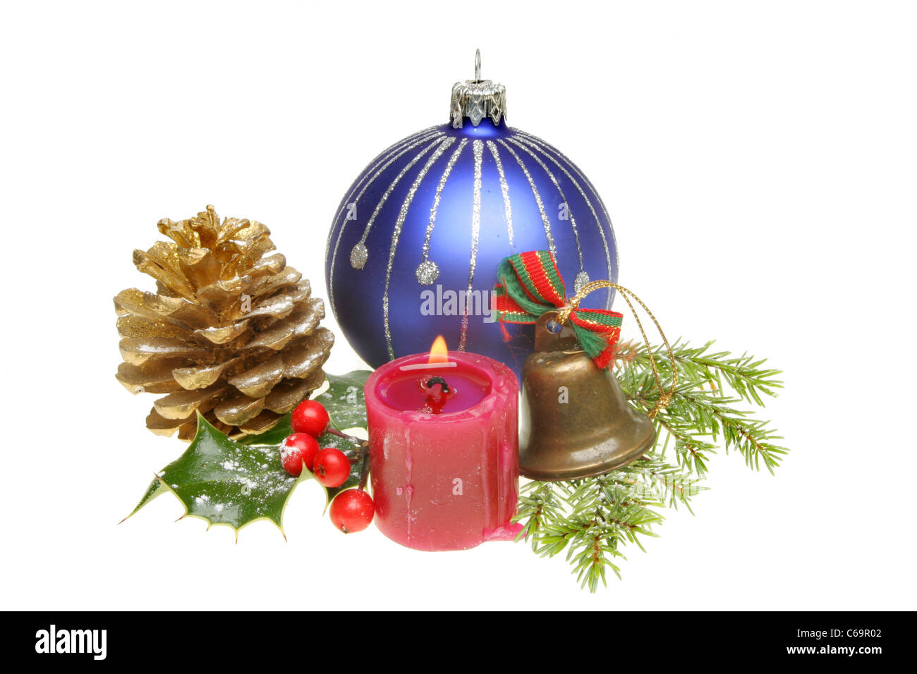 Christmas ornaments and snow dusted seasonal foliage with a burning candle - Stock Image