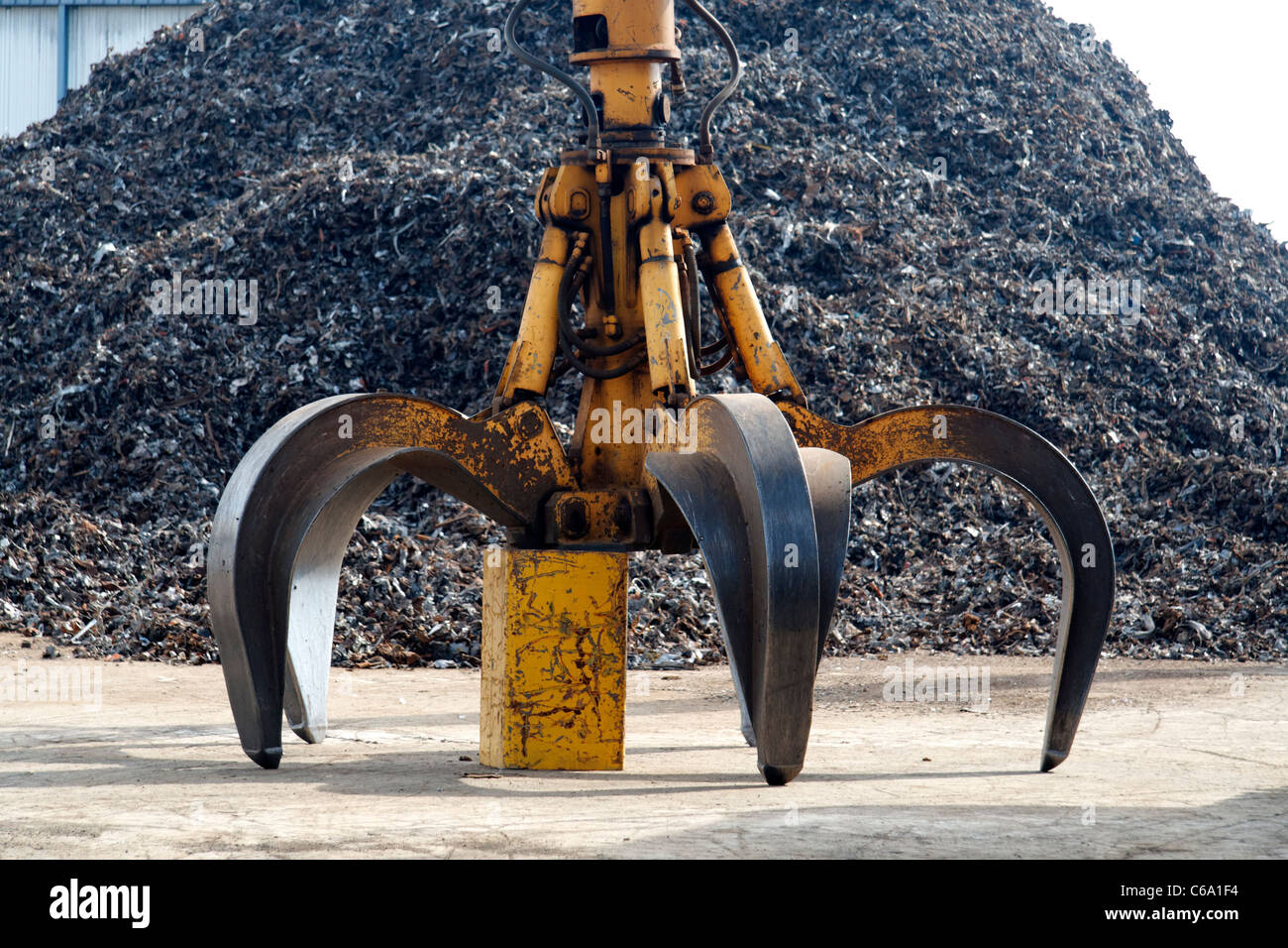 Claw clamp in front of scrap metal (Normandy, France). - Stock Image