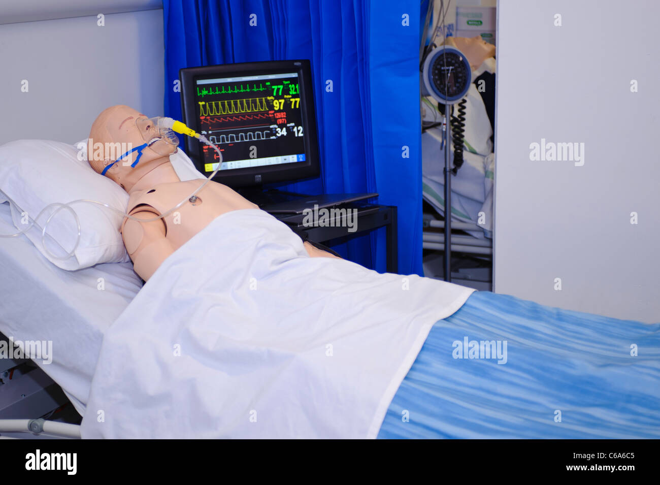 dummy patient simulated mannequin wearing oxygen mask in hospital bed vitals status monitor in background - Stock Image