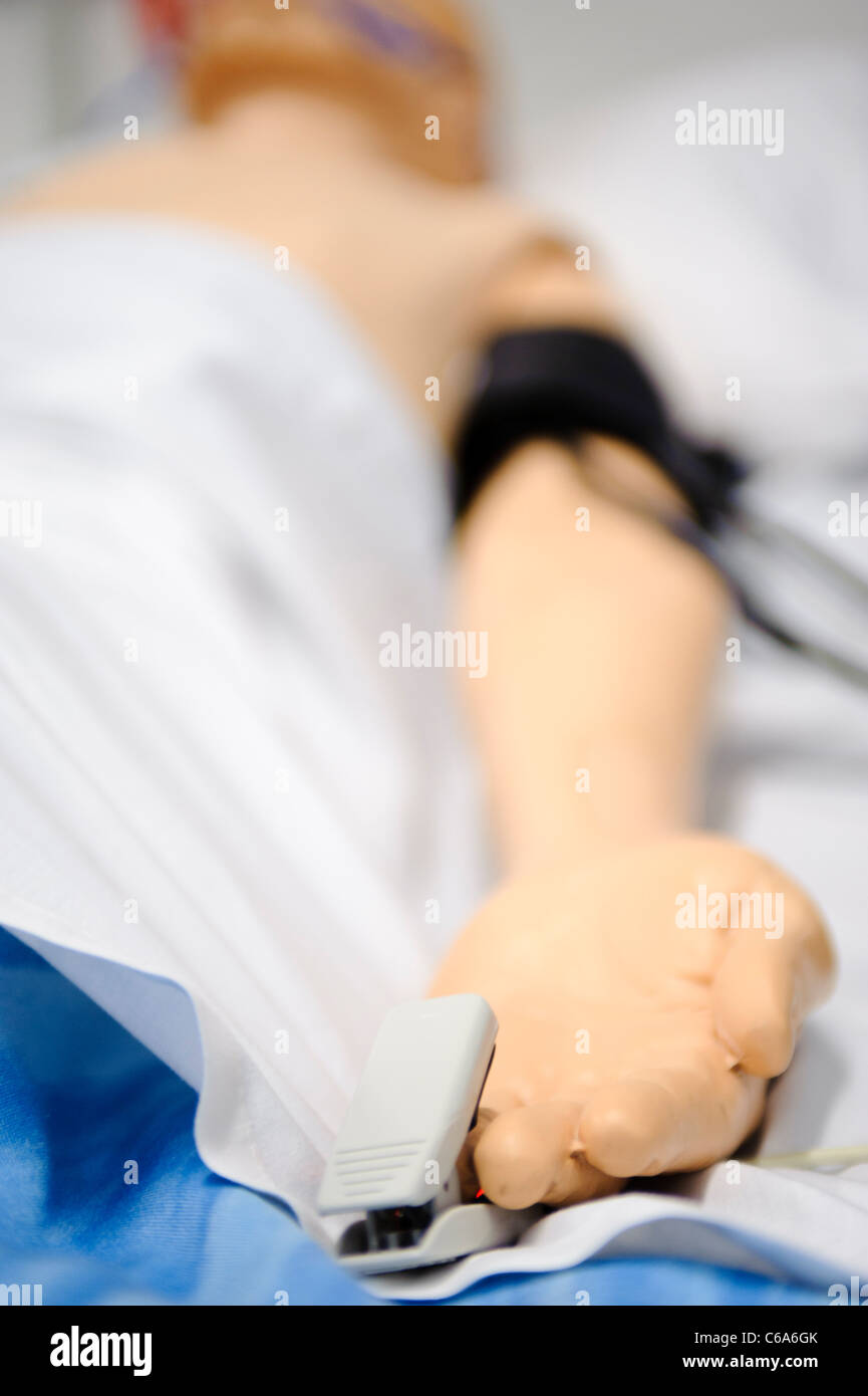 dummy mannequin patient hospital bed blood pressure monitor and oxygen mask - Stock Image