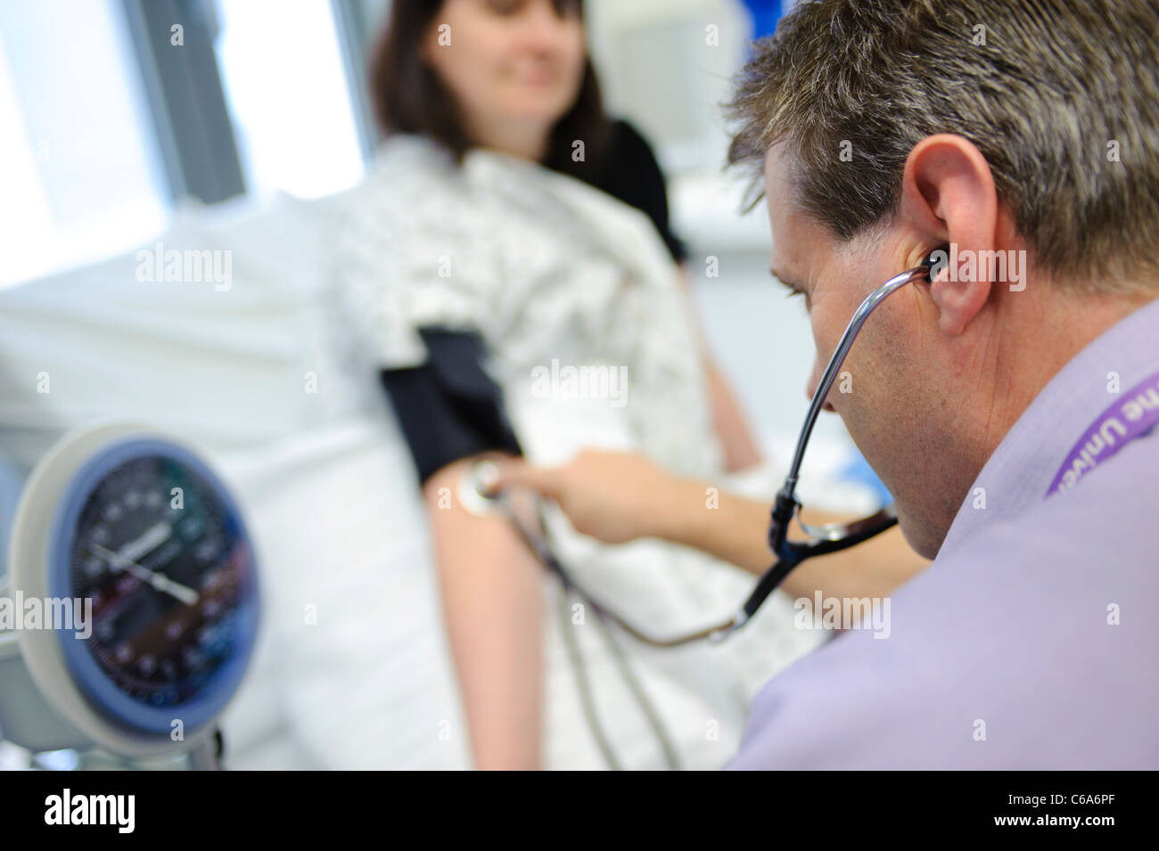 doctor checking blood pressure of patient and using stethoscope hospital bed patient and doctor not identifiable - Stock Image