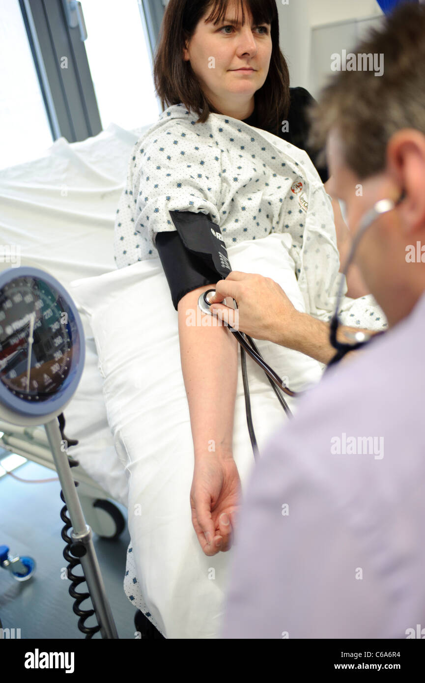 patient arm blood pressure pulse monitored by doctor stethoscope hospital ward - Stock Image