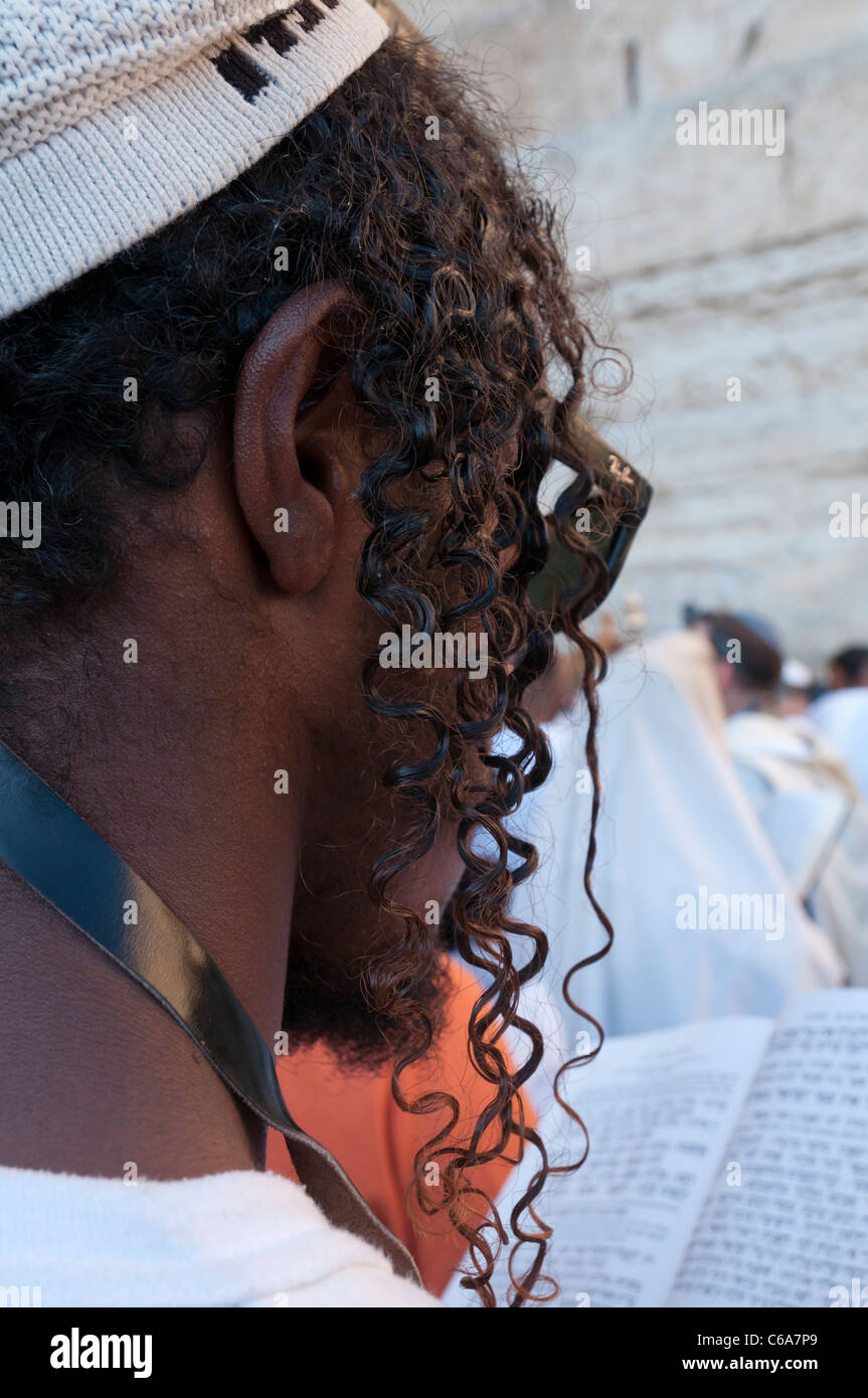 portrait of an ethiopian Jew with braids praying at the Western Wall. jerusalem Old City - Stock Image