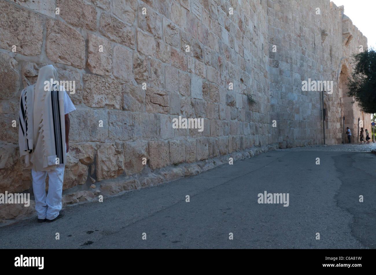 Jew with prayer shawl praying by City Walls near Zion Gate. Jerusalem Old City. Israel - Stock Image