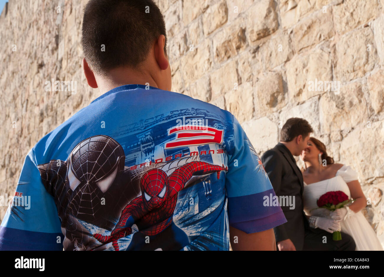 Boy wearing spider man T shirt with groom and bride in bkgd. jaffa Gate. Jerusalem - Stock Image
