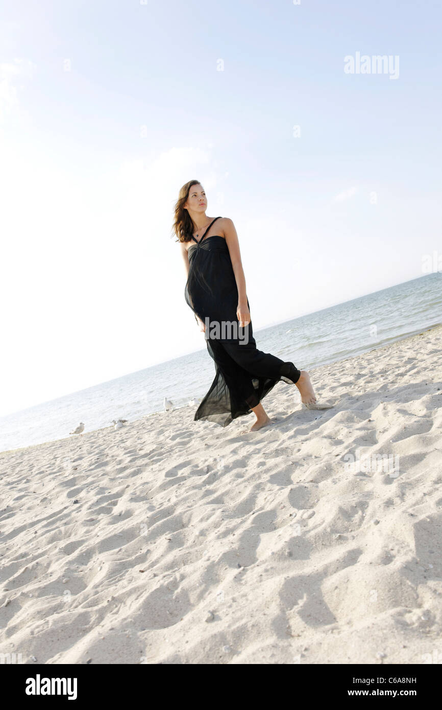 Young woman, 20+, standing in a long dress on the beach, lifestyle, sensuality, space, lightness, Niendorf at the - Stock Image