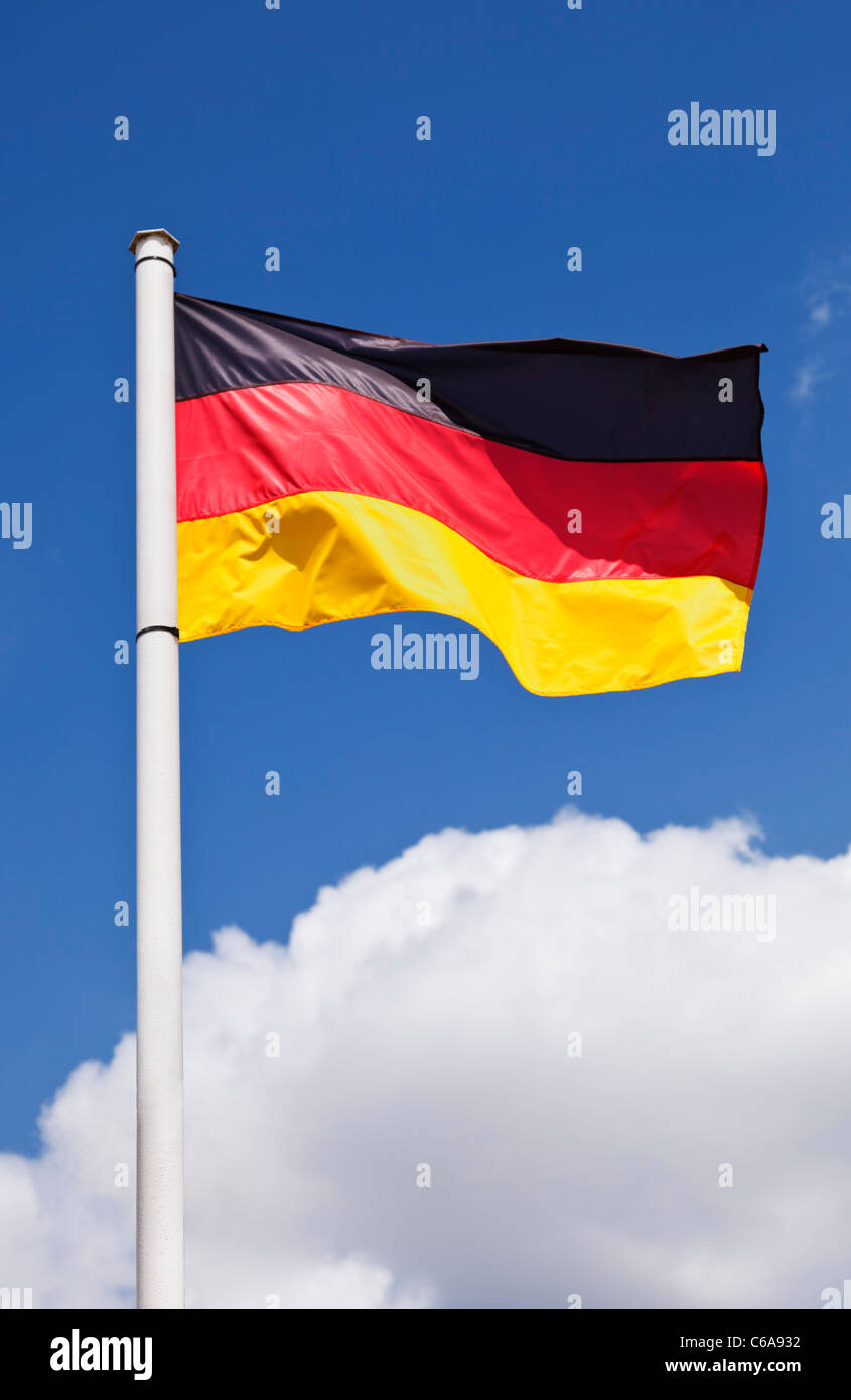 Colourful German flag against a blue sky - Stock Image