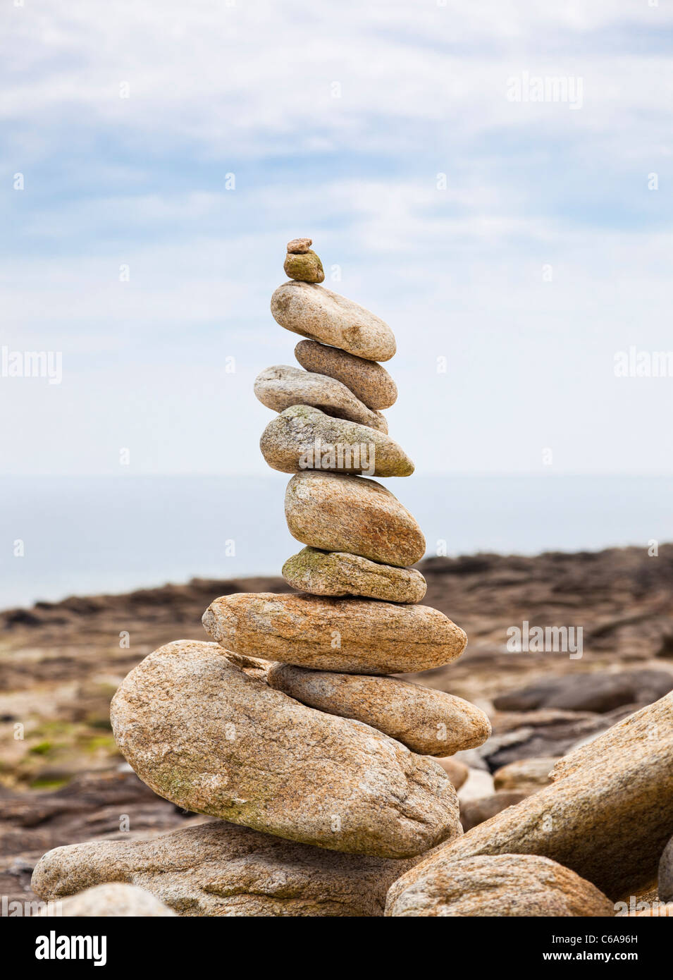 Pebbles balanced in a pile on a beach - Stock Image