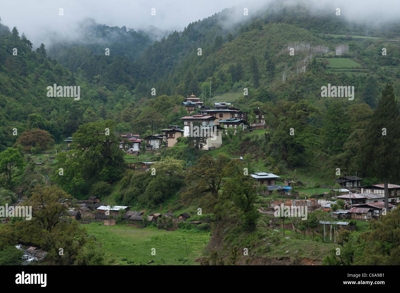 view of tipycal village surrounded by hills and forest. bhutan - Stock Image