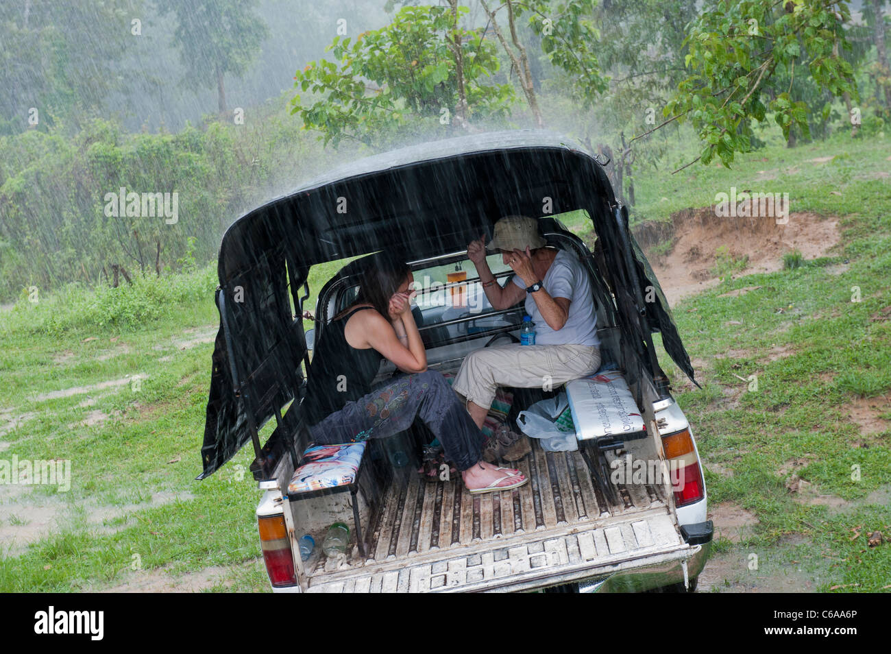 Two women take shelter from heavy rain in the back of a 4x4 vehicle Thailand Asia - Stock Image