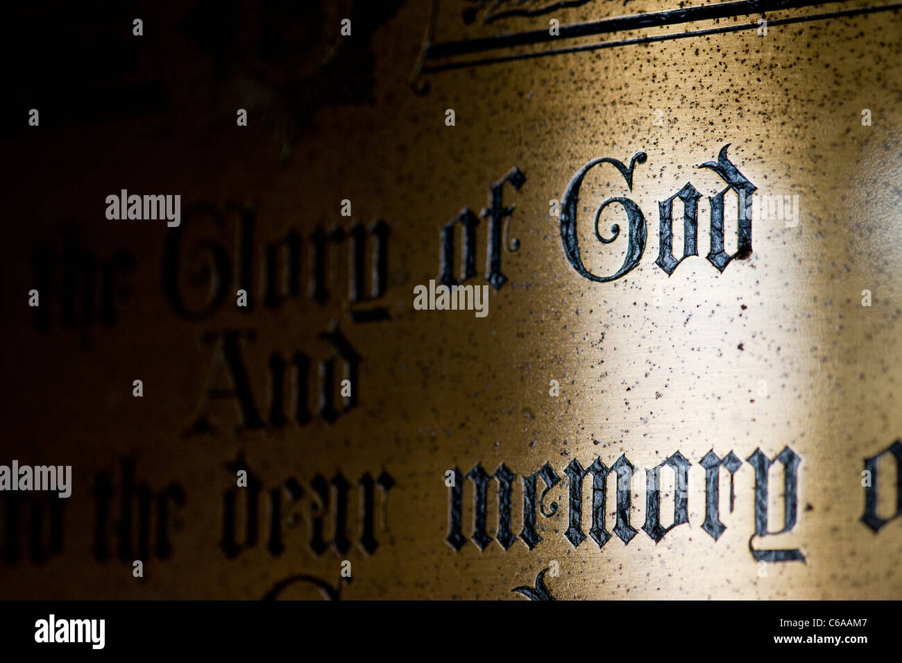 Brass church plaque with the word GOD highlighted by sunlight Stock Photo