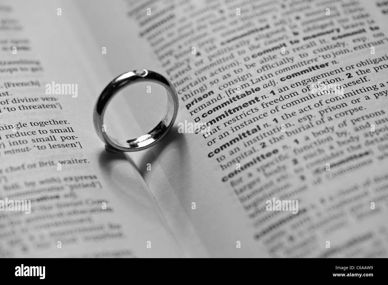 Love and Commitment - conceptual image of a wedding ring placed by the word commitment.  The shadow forms a heart - Stock Image