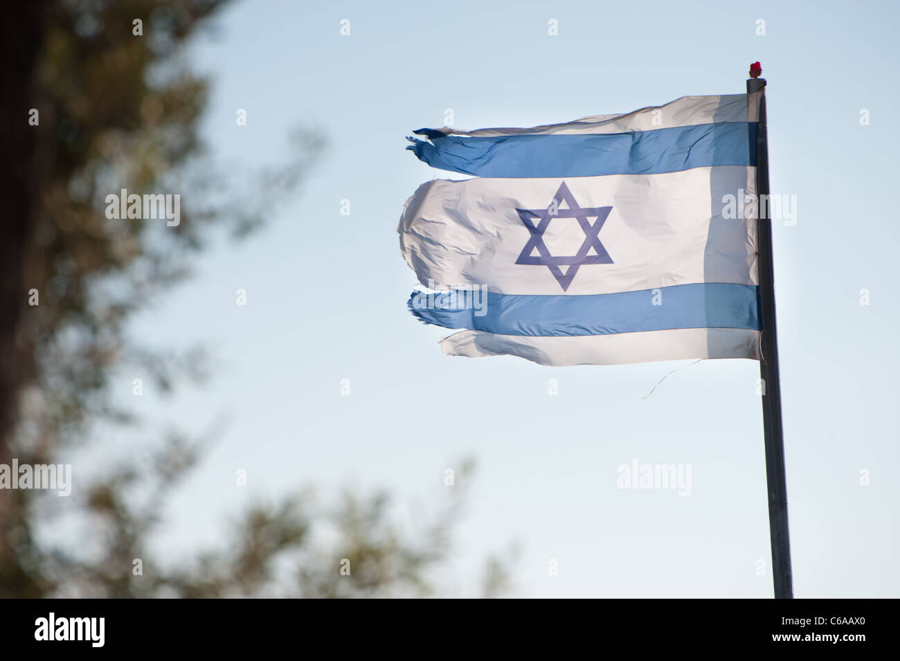 A ragged Israeli flag flies over the Jewish settlement of Beit Hoshen on the Mount of Olives in East Jerusalem. - Stock Image