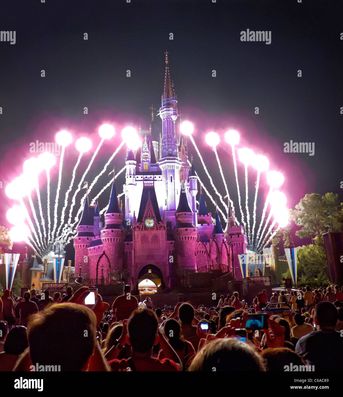 Fireworks explode over Cinderella's Castle in Magic Kingdom, Disney World, FL, while light show plays across castle's - Stock Photo