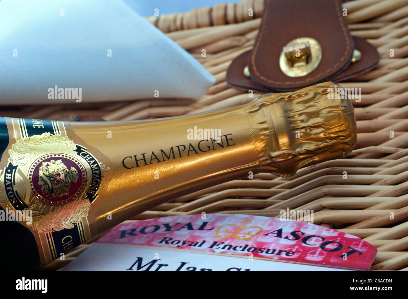 Close view on Champagne bottle and admission badge on wicker hamper at luxury alfresco Royal Ascot after the races - Stock Image