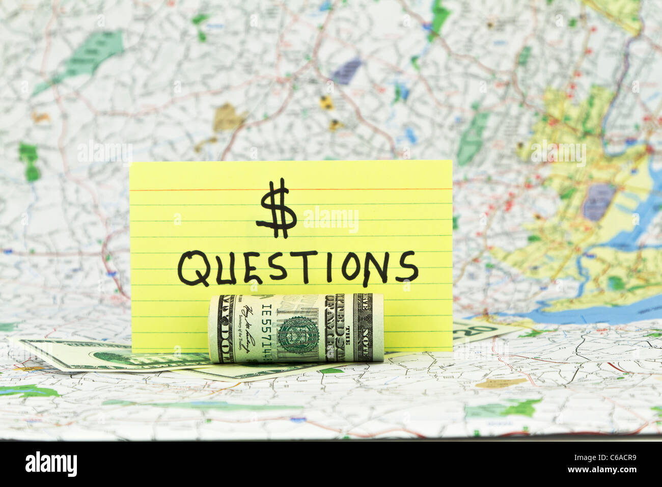 Yellow card with dollar sign and text, questions, with currency under and in front. Money questions card with map - Stock Image