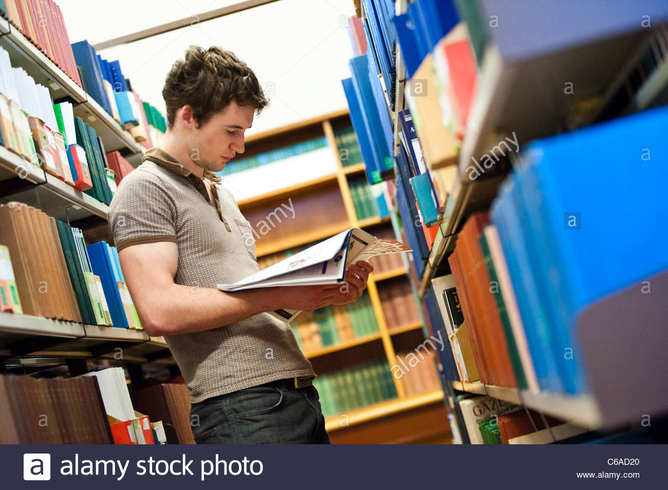 university library book shelf stacks student reading in background - Stock Image