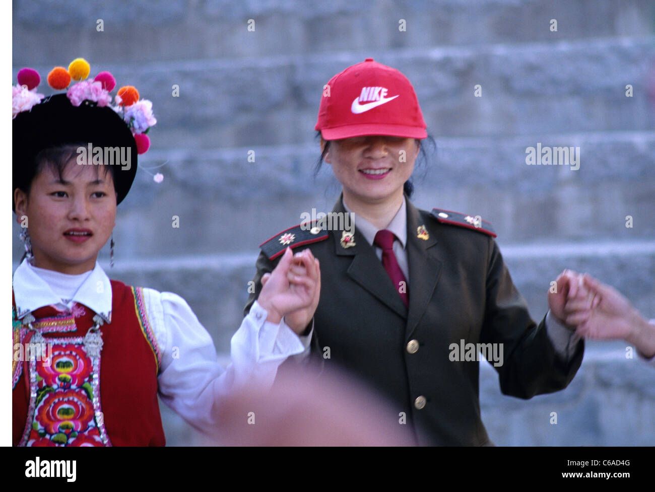 chinese female soldier wearing nike baseball cap dances with girls wearing  traditional clothes at chinese festival in Beijing. f12dfac7b66