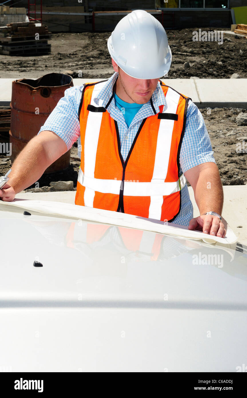 Architect On Site Checking Drawings On The Hood Of His Truck - Stock Image