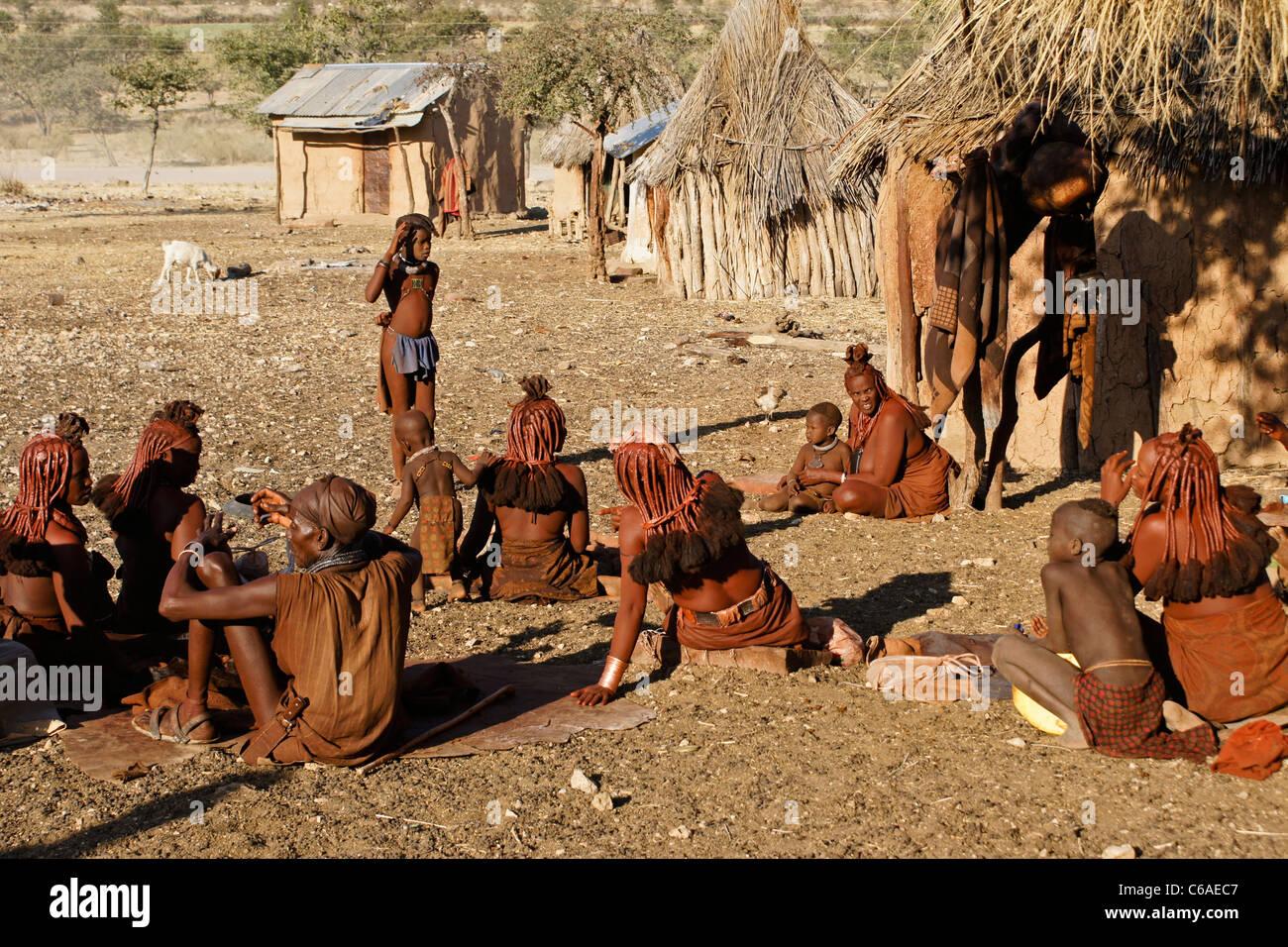 Himba people in their village near Opuwo, Namibia - Stock Image