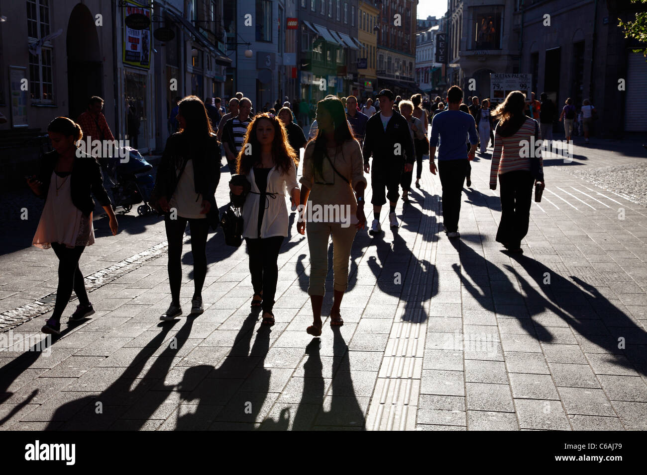 Long shadows from people on their way on the busy pedestrian street Strøget in Copenhagen backlit by the low - Stock Image