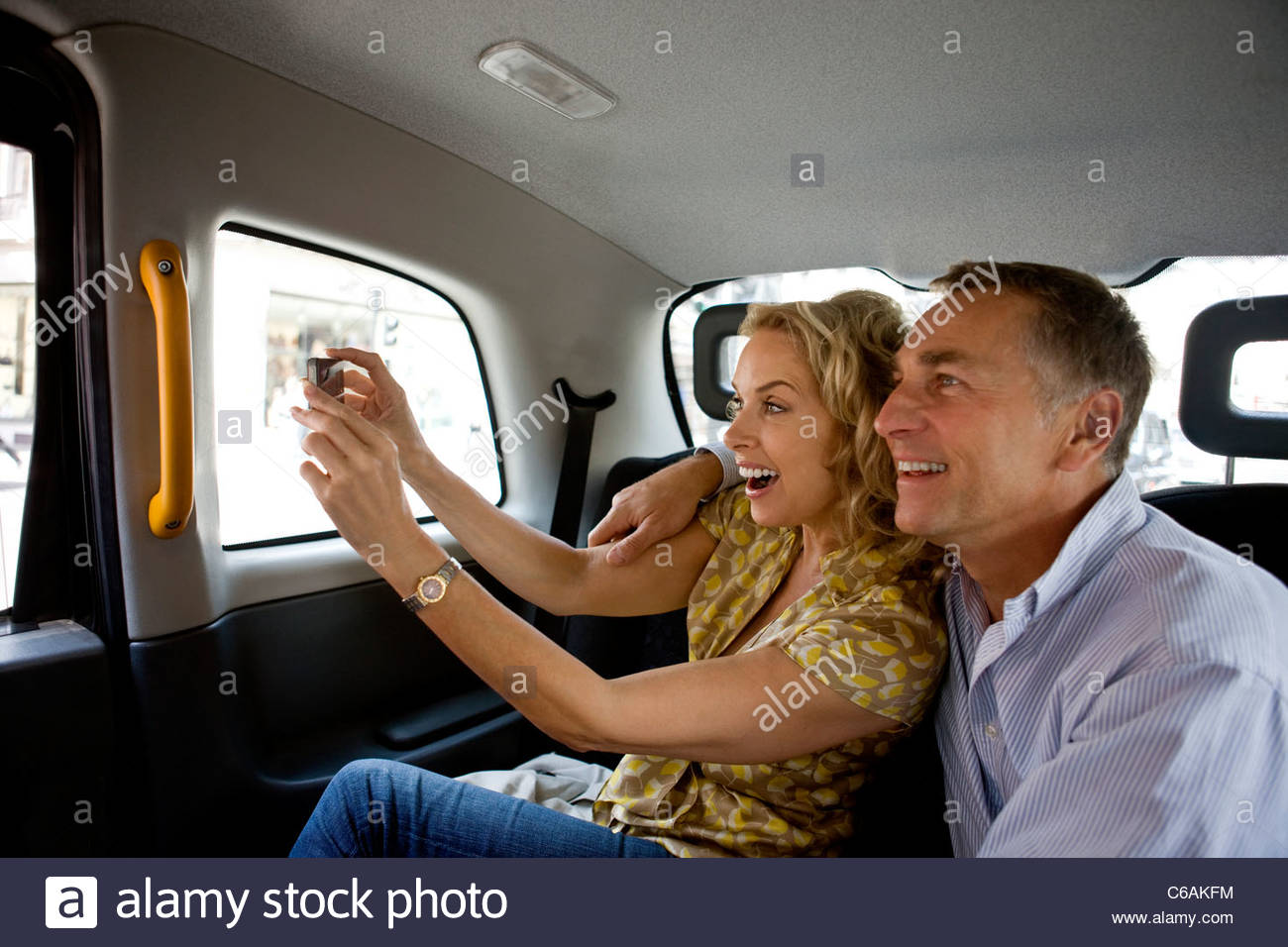 A middle-aged couple in a London taxi, taking a photograph - Stock Image