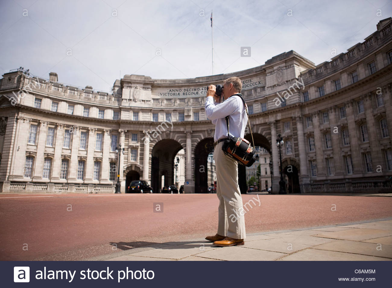 A middle-aged man standing by Admiralty Arch, taking a photograph - Stock Image