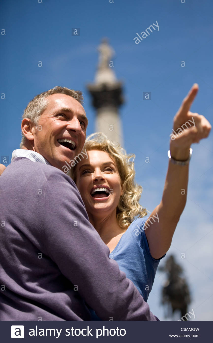 A middle-aged couple standing in front of Nelson's column, woman pointing - Stock Image