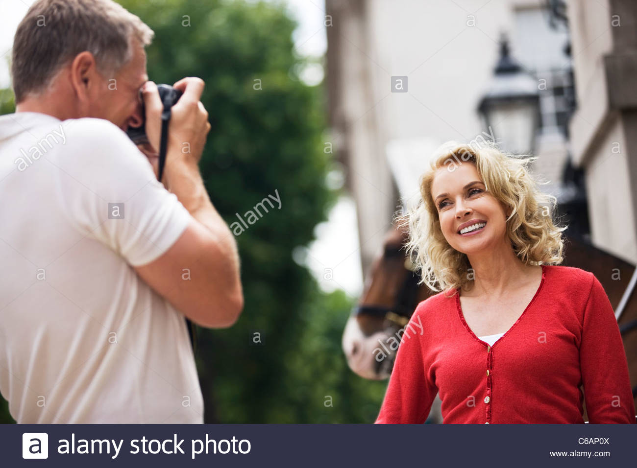 A middle-aged man taking a photograph of his partner in front of Horse Guards - Stock Image