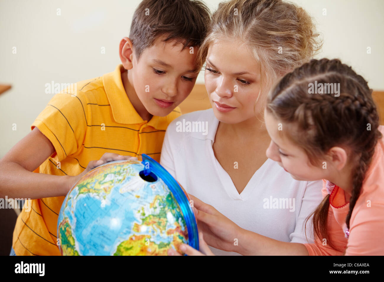 Portrait of cute classmates and teacher looking at globe at geography lesson - Stock Image