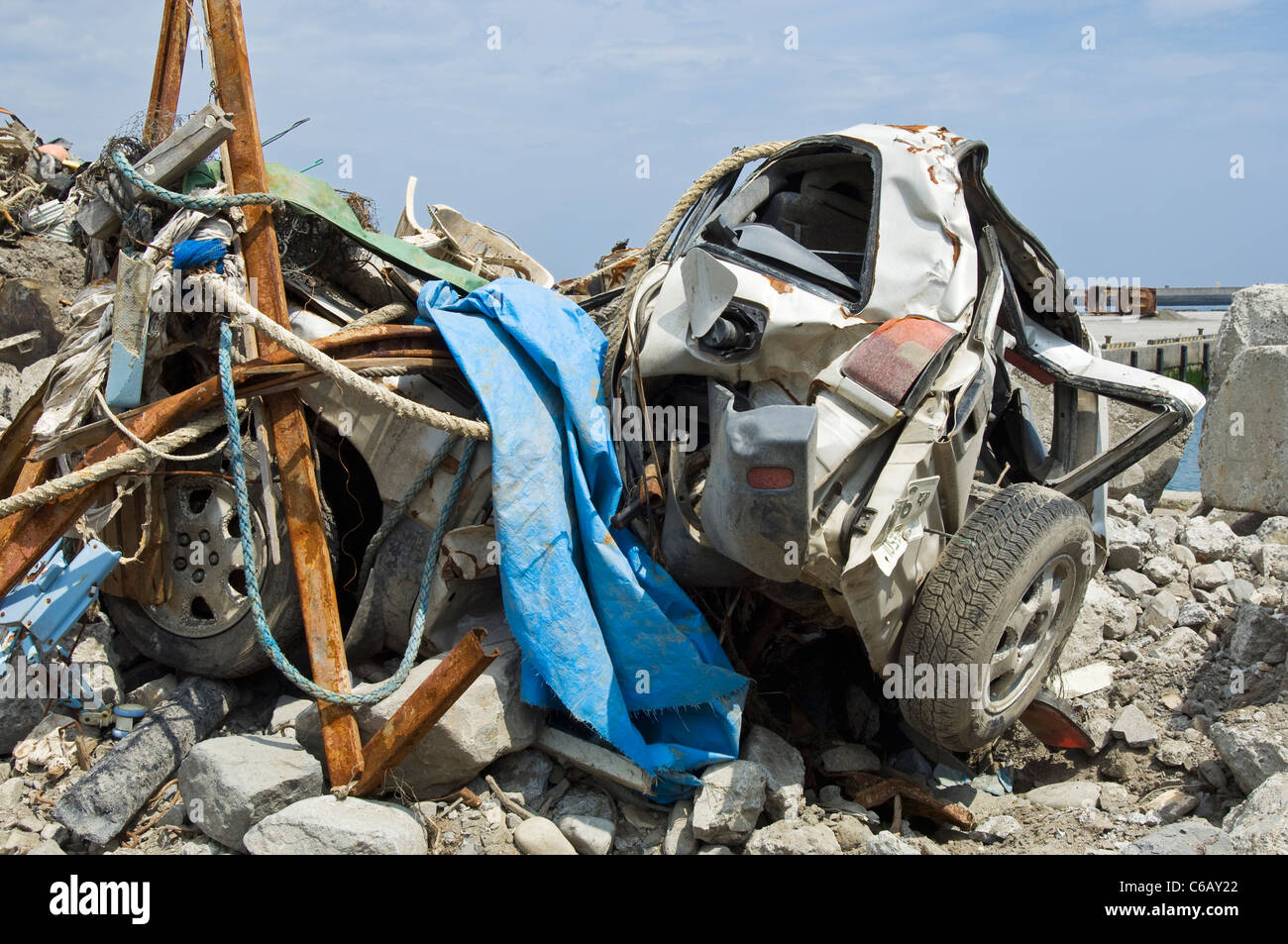 Debris and a car totally destroyed by the tsunami - Stock Image