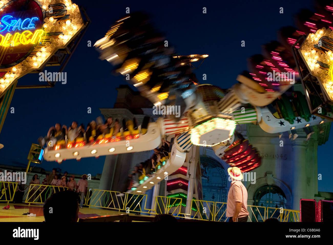 Striped shirted worker watching a fairground ride whirl overhead - Stock Image