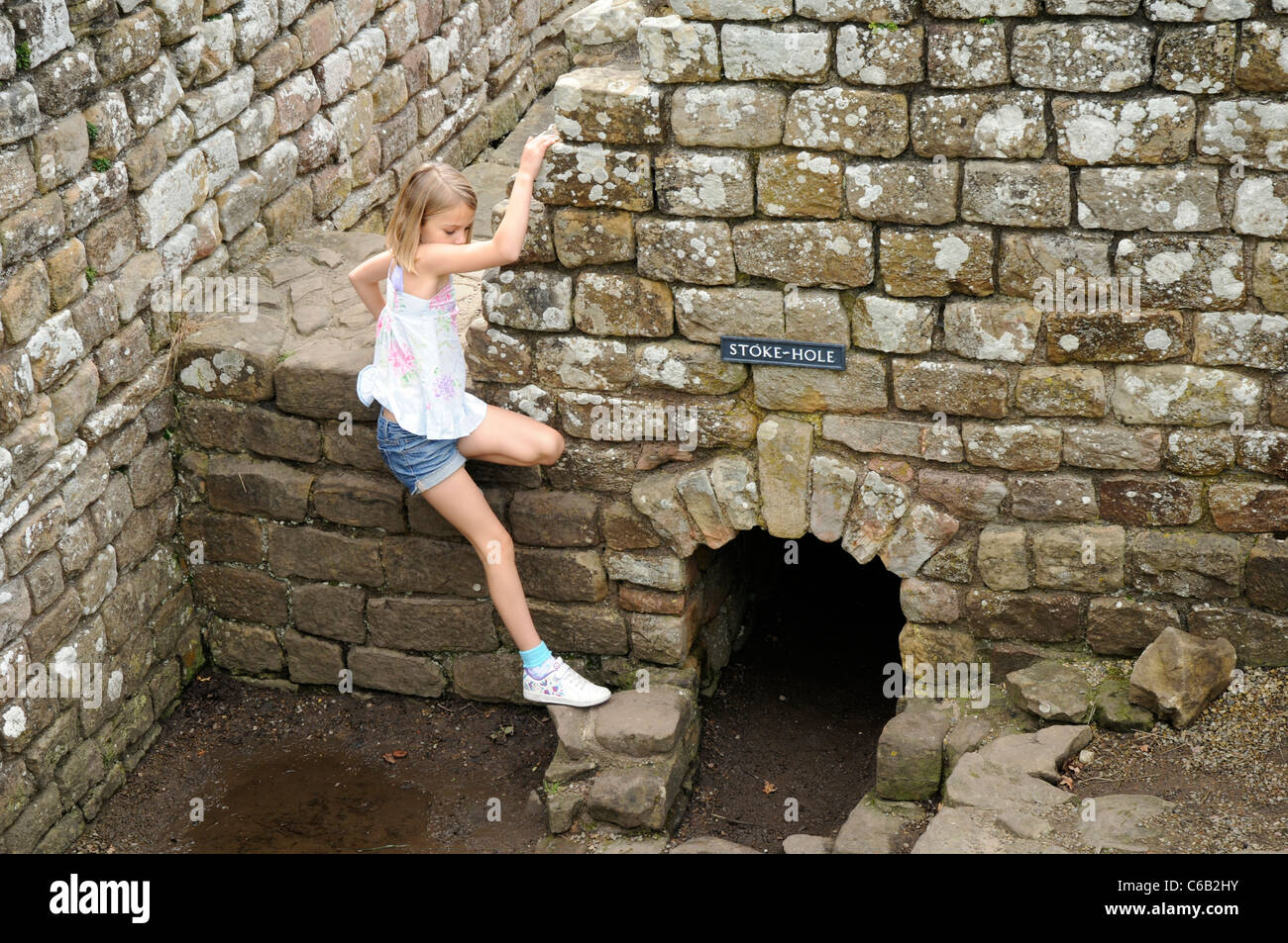 Young girl climbing over Roman Bath House ruins at Chesters Fort, on Hadrian's Wall, England. - Stock Image