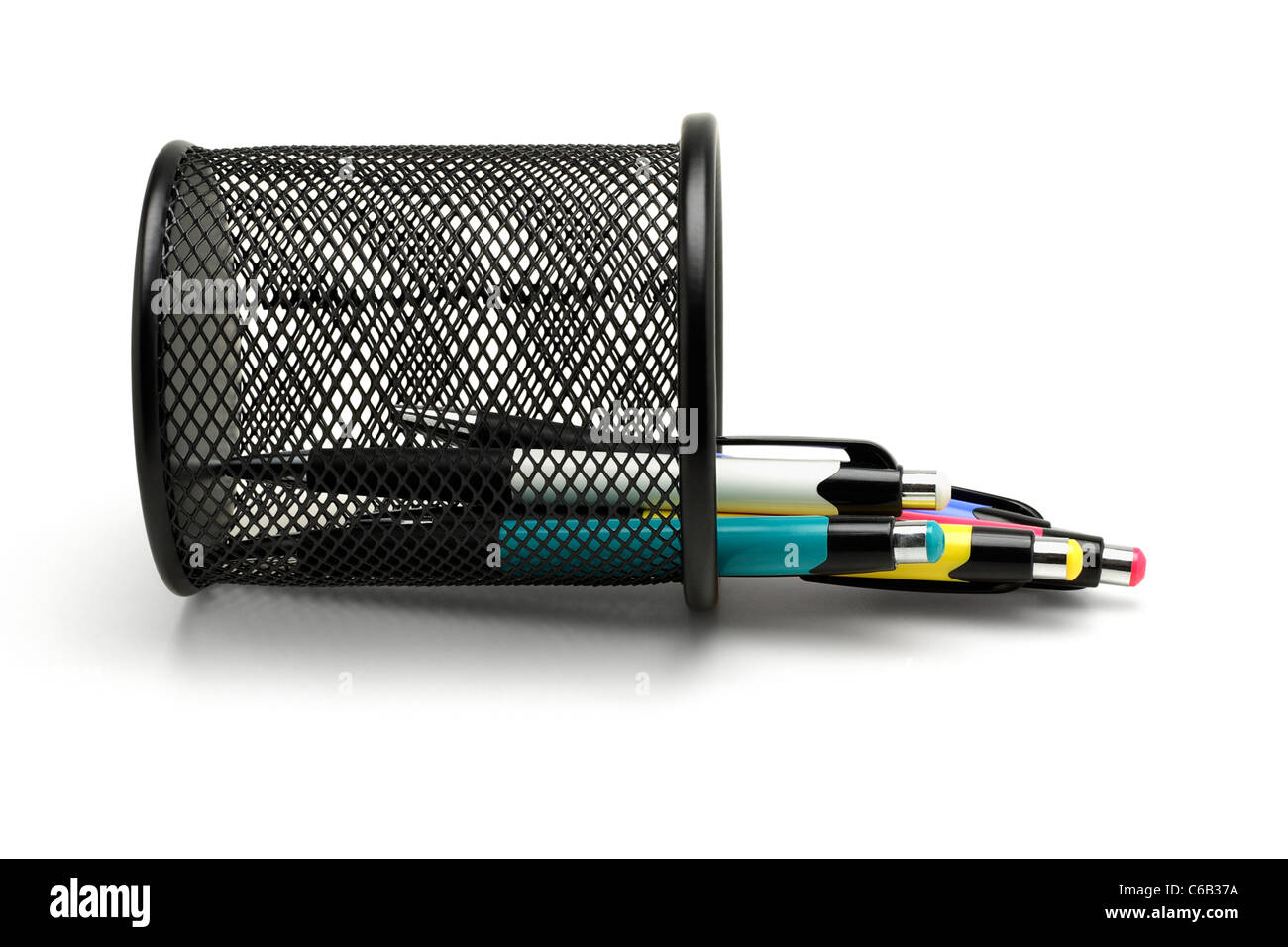Multicolor ball point pens spilled out from fallen black basket container Stock Photo