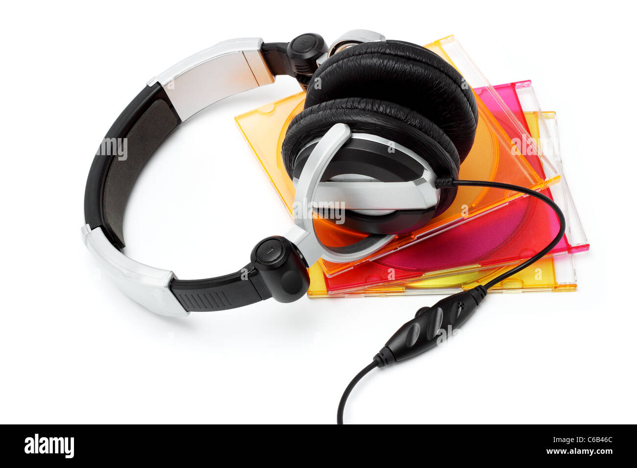 Stereo headphone and compact disks in colorful plastic cases on white background Stock Photo