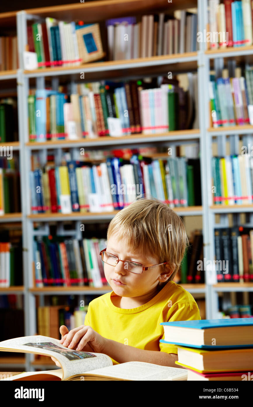 Portrait of cute schoolkid reading book in the library - Stock Image