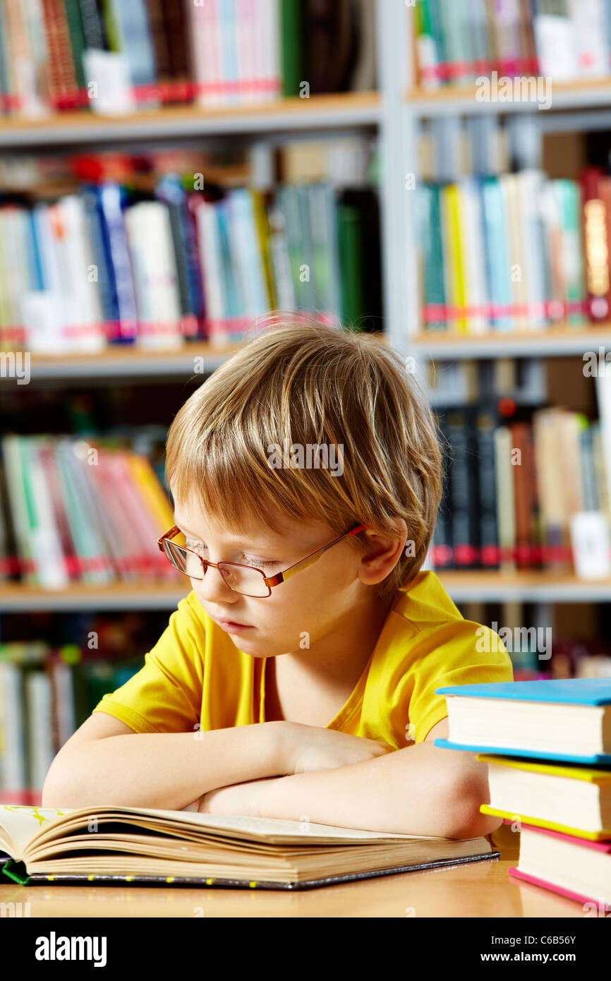 Portrait of cute schoolkid reading in the library - Stock Image