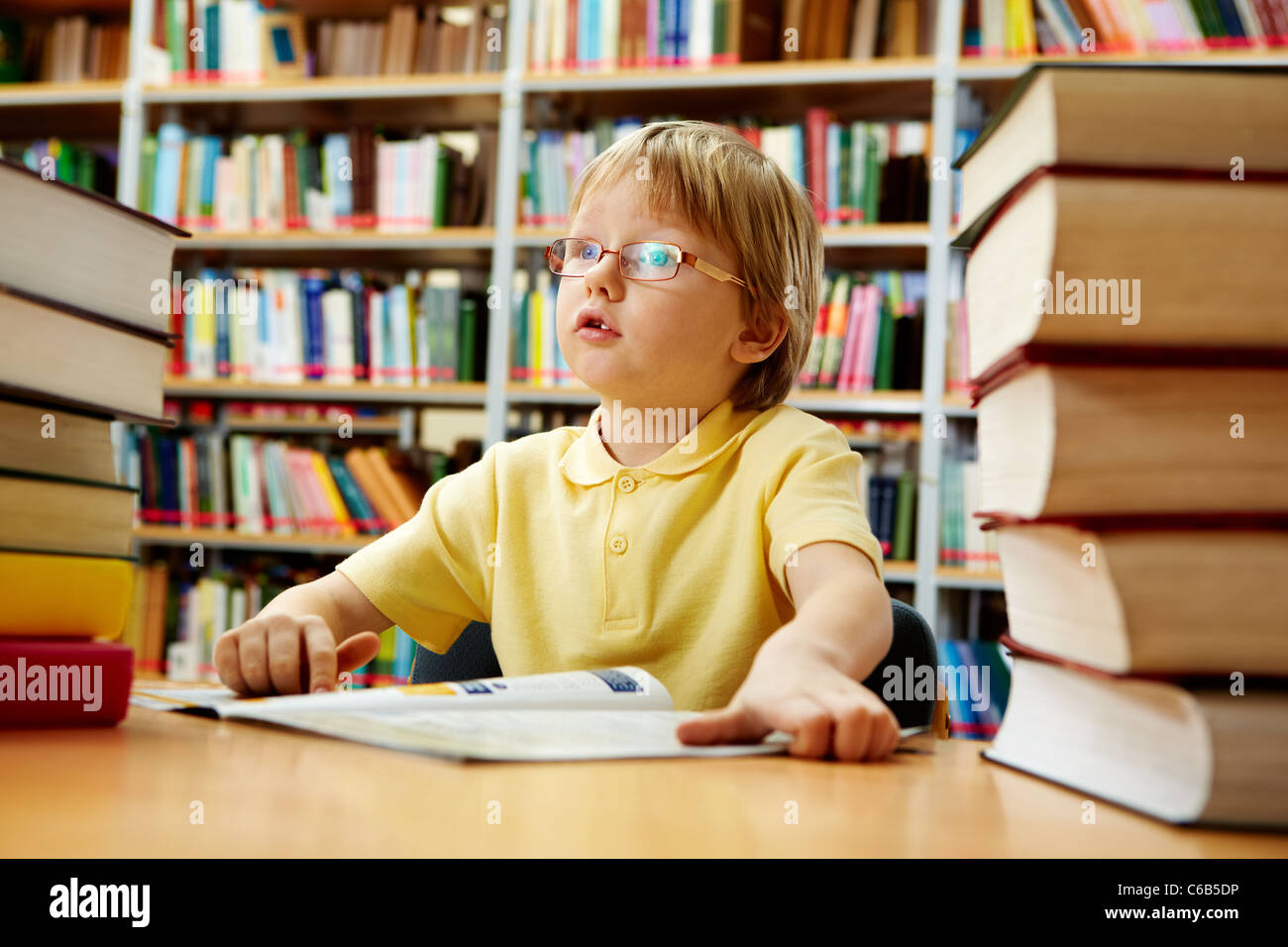 Portrait of interested schoolkid reading book in the library - Stock Image