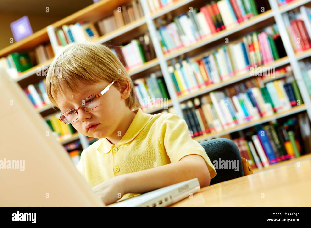 Portrait of serious schoolkid working with laptop in the library - Stock Image