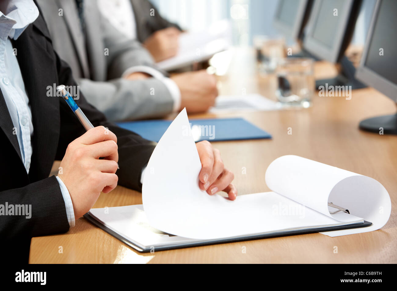 Human hand with pen holding paper during written work - Stock Image