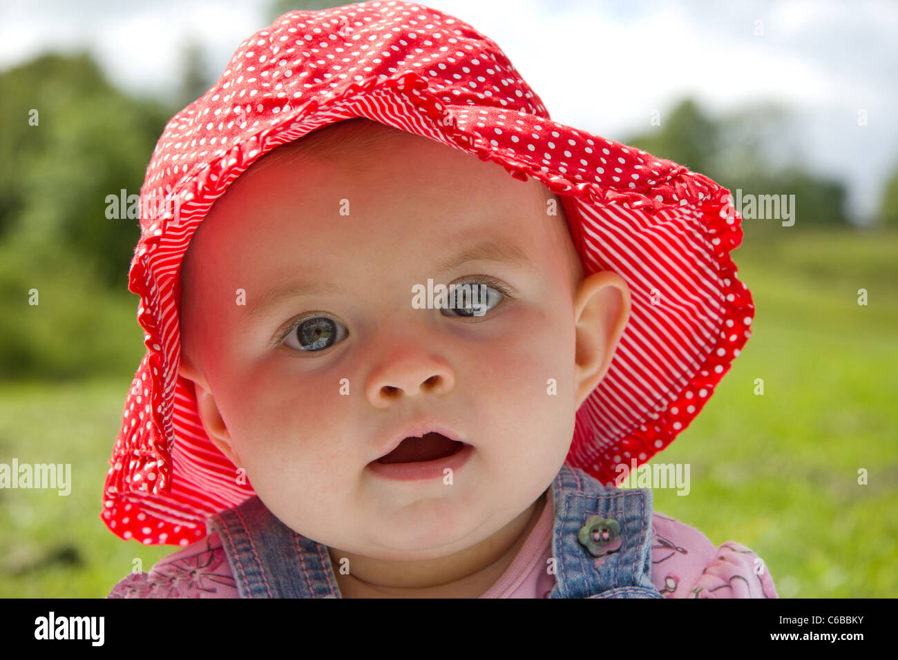 Gorgeous baby girl sitting in a park wearing a cute summer hat - Stock Image