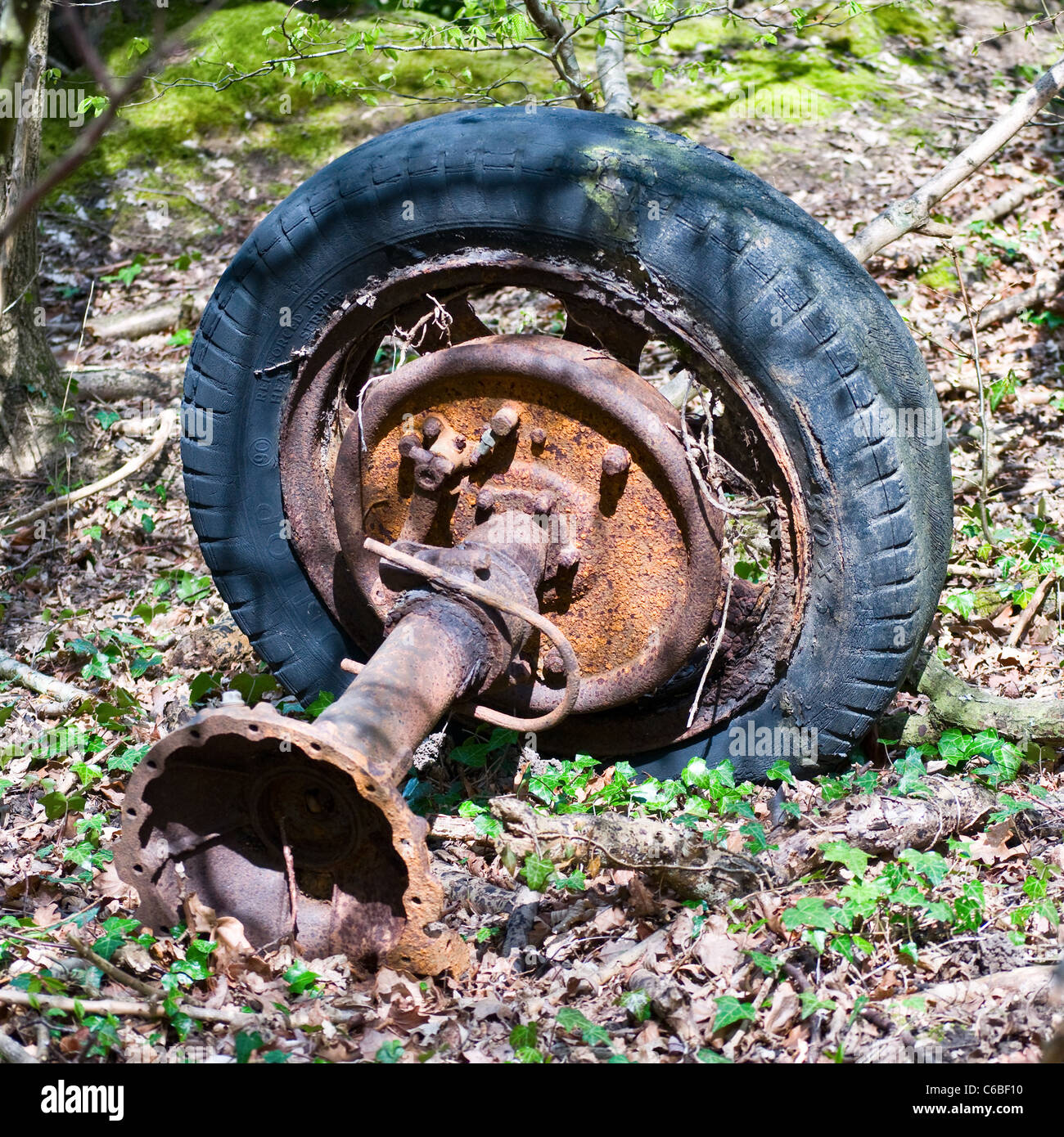 An old rusty tractor wheel, tyre and axial in woodland - Stock Image