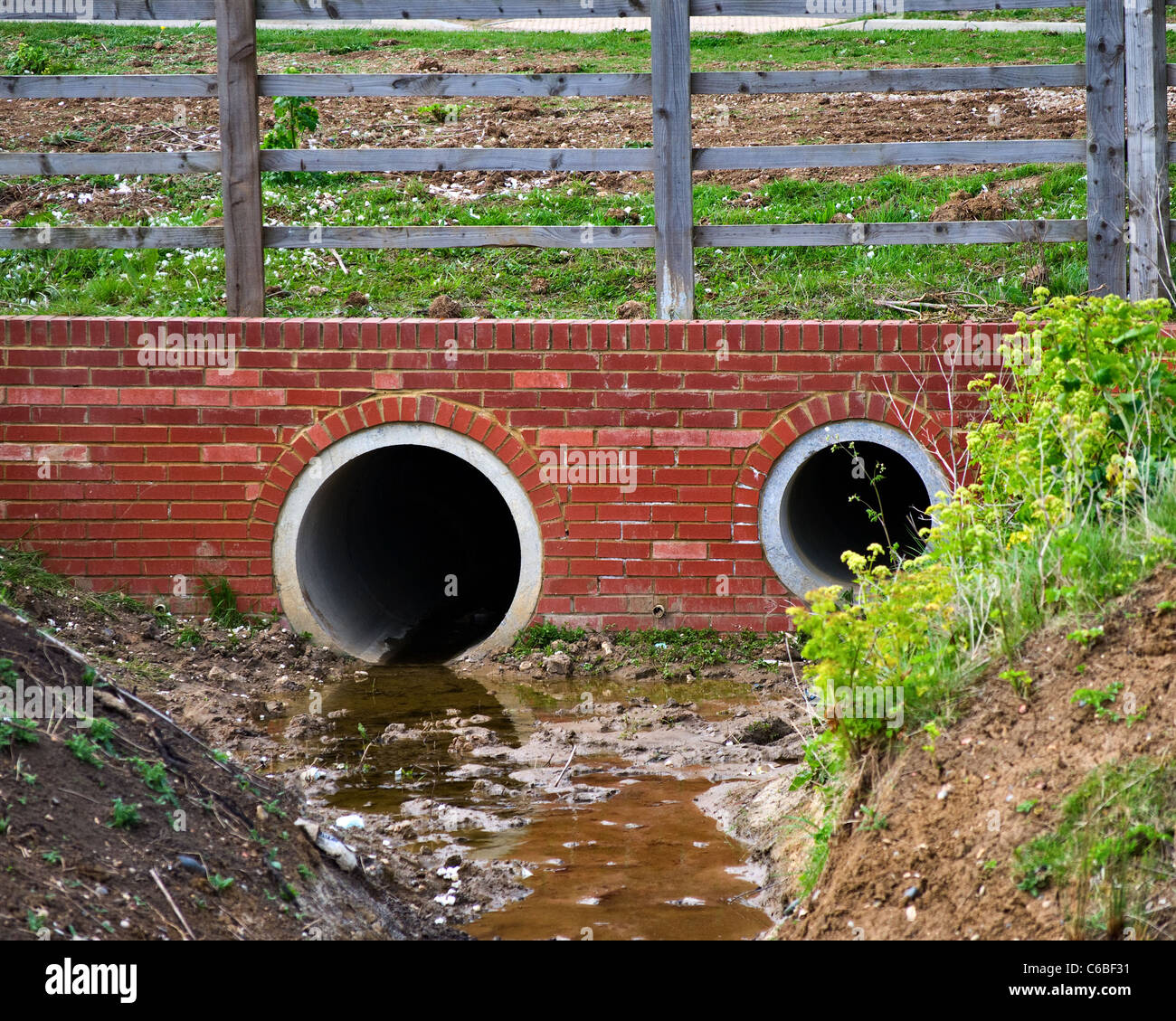 Two drainage pipes newly laid ready to take the new road above - Stock Image