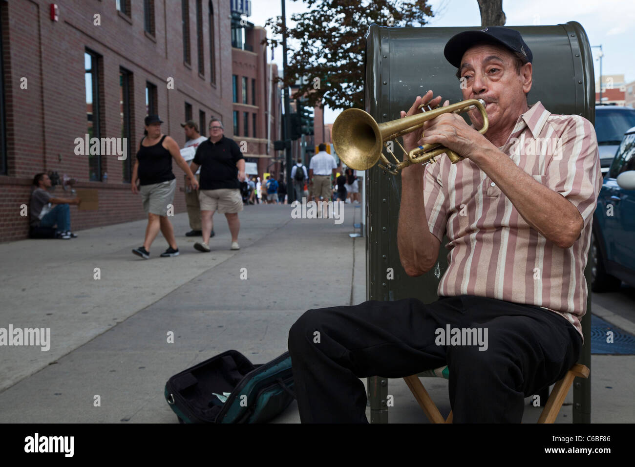 Denver, Colorado - A street musician plays the trumpet for tips as fans arrive at Coors Field for a baseball game. - Stock Image