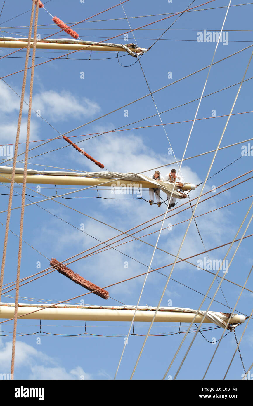 Crew working on the sails of a ship berthed at the Tall Ships Race 2011 in Greenock, Scotland, UK - Stock Image