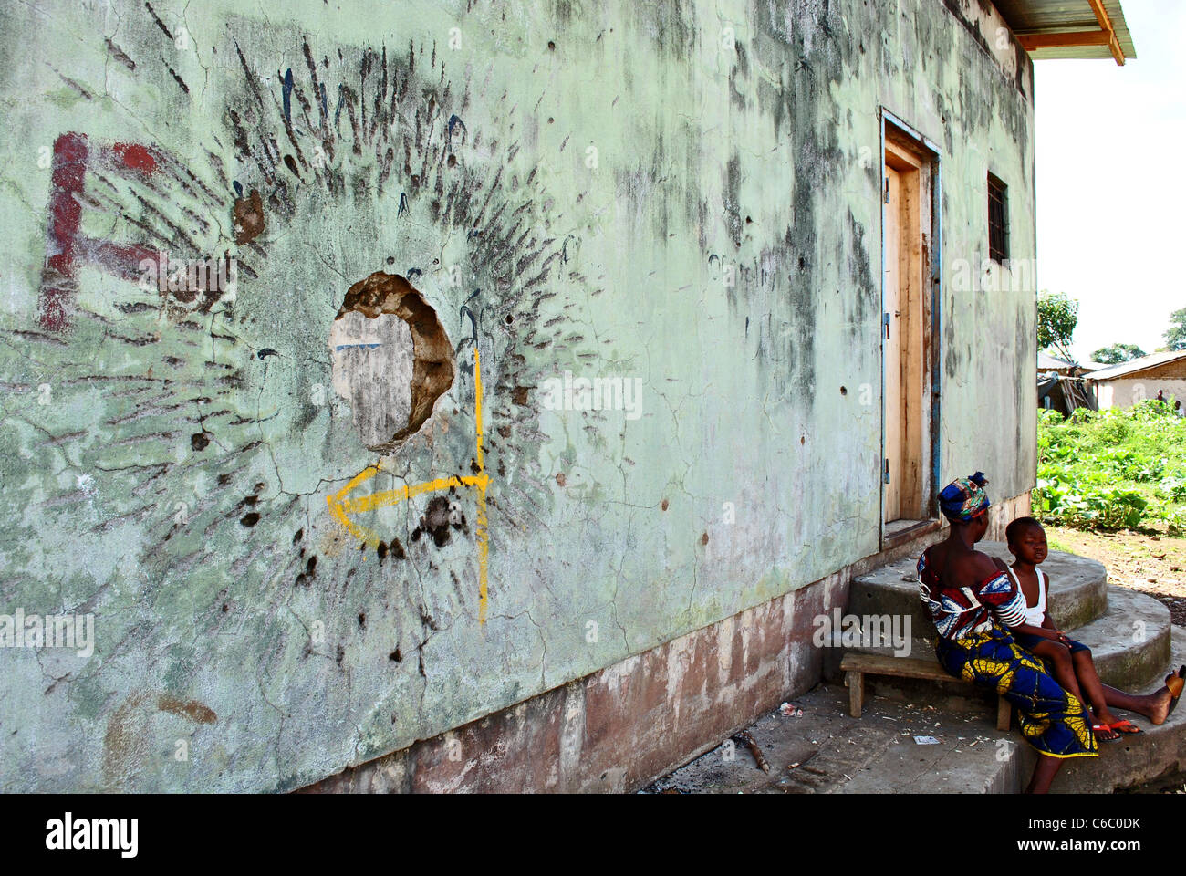 A mother and child sit beside a hole in their house, damaged during the civil war in Liberia, West Africa - Stock Image