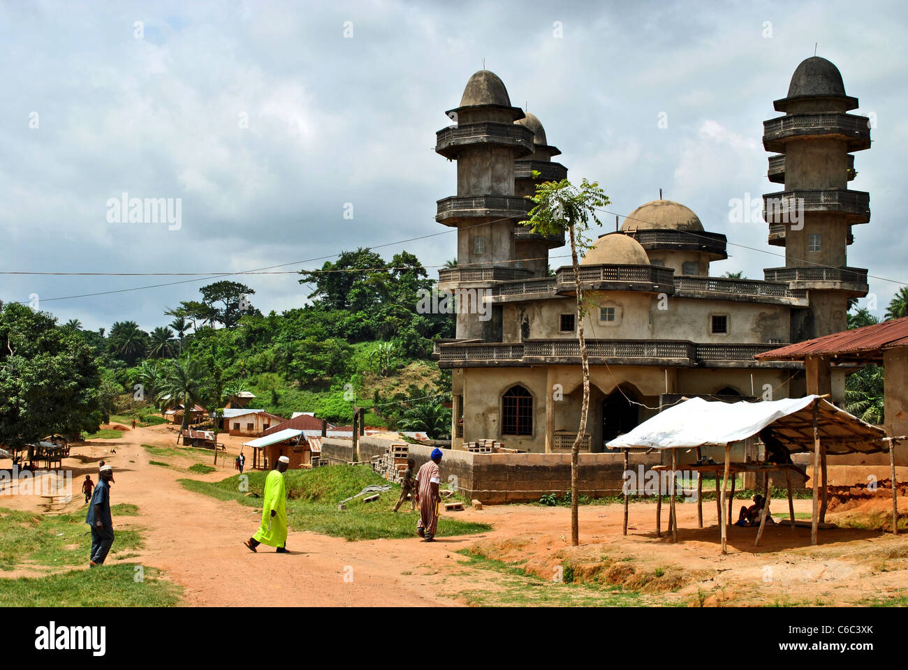 Muslims cross a road to go to the mosque in a small village between Kolahun and Bolahun, Liberia, West Africa - Stock Image