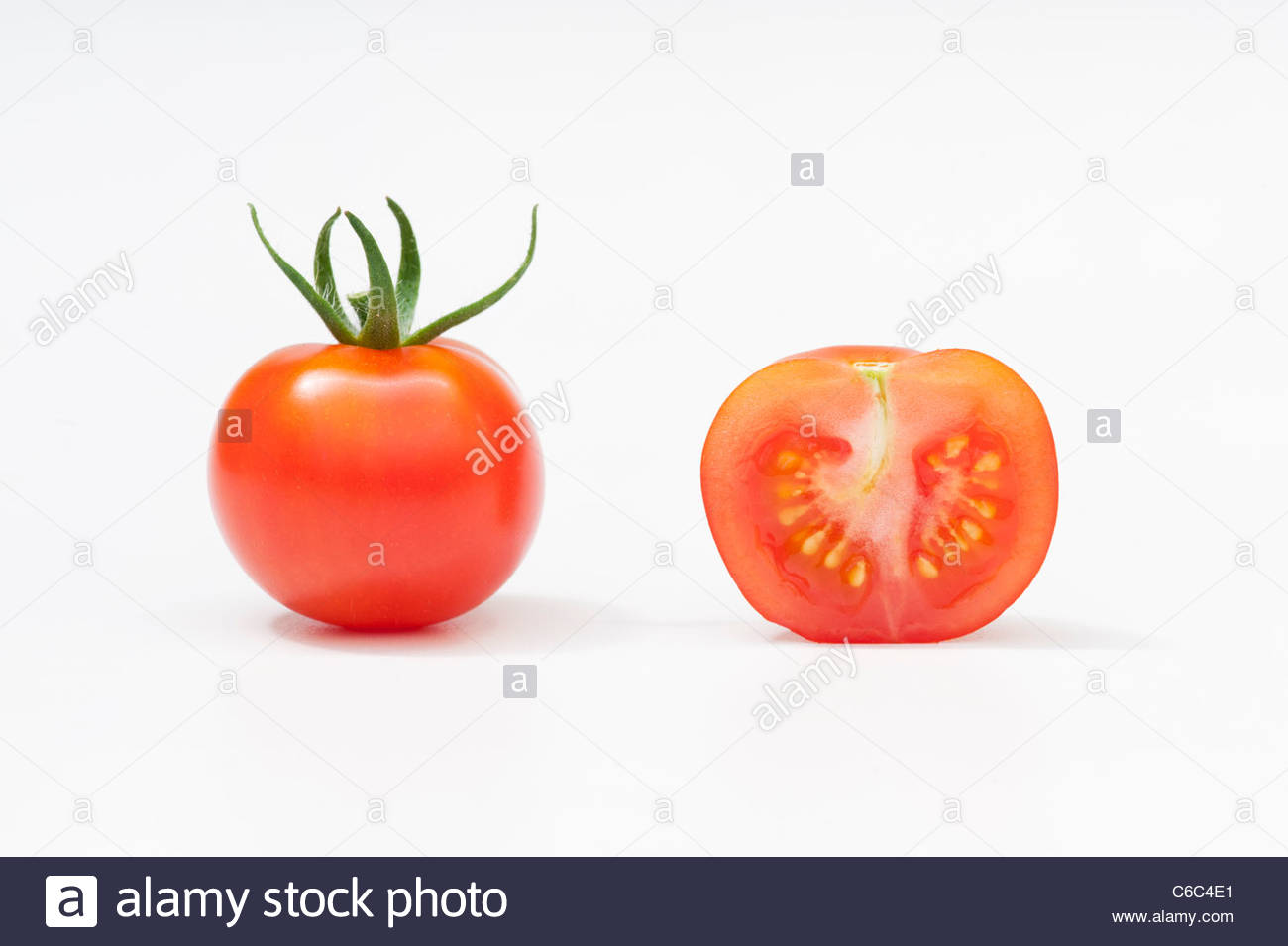 Whole And Cross Section Of A Tomato Showing Seeds On White